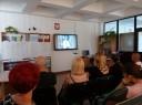 Uczestnicy oglądają film szkoleniowy